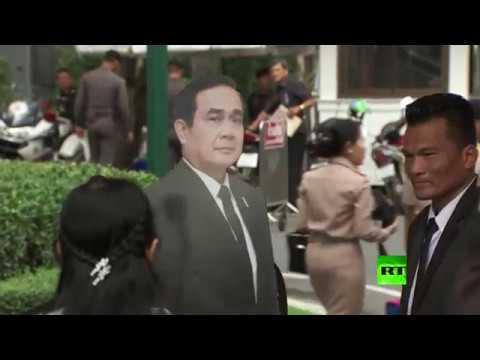 مجسم كرتوني بصورة رئيس وزراء تايلاند يتحدث مع الصحافيين