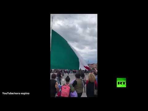 مكسيكون يساعدون أفراد الجيش في الإمساك بعلم الدولة